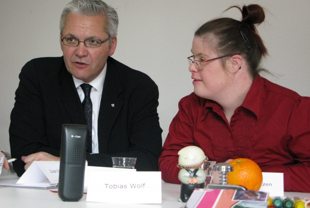 Angela Fritzen and Hubert Hüppe sitting at a table and talking.